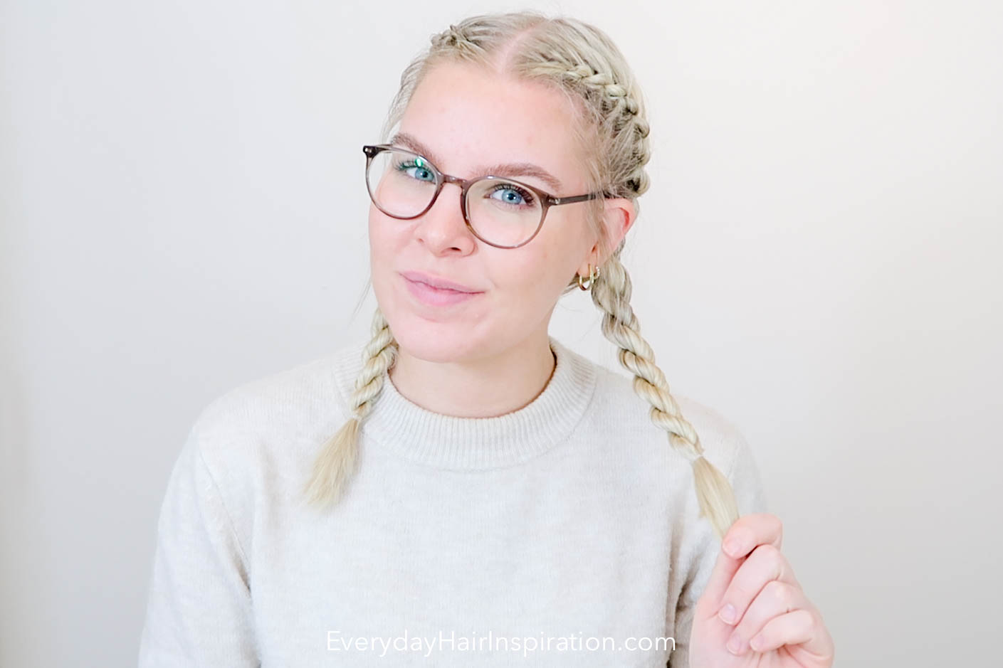 Blonde girl seen from the front, looking into the camera with her hair braided into double French rope braids, holding one braid in her hand.