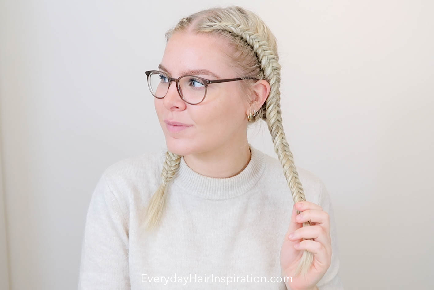 Blonde girl looking to the side, with double dutch fishtail braids in her hair, holding 1 braid in the left hand.