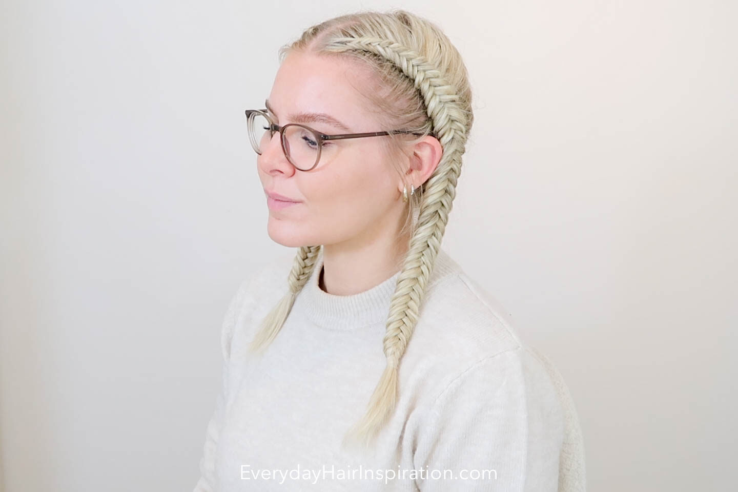 Blonde girl looking to the side, with double dutch fishtail braids in her hair.