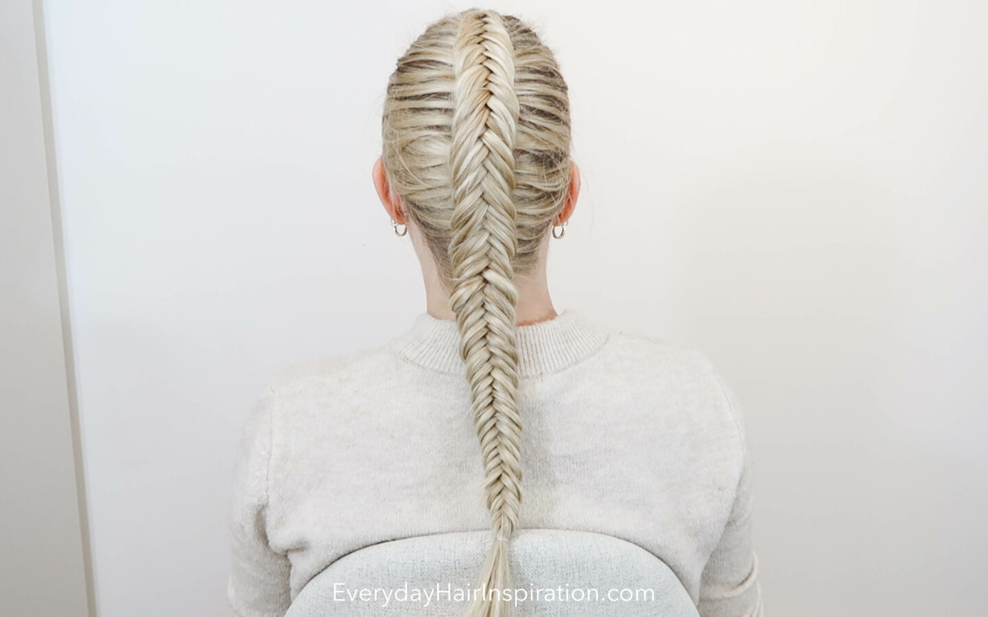 Blonde girl with her back to the camera with a single dutch fishtail braid in her hair.