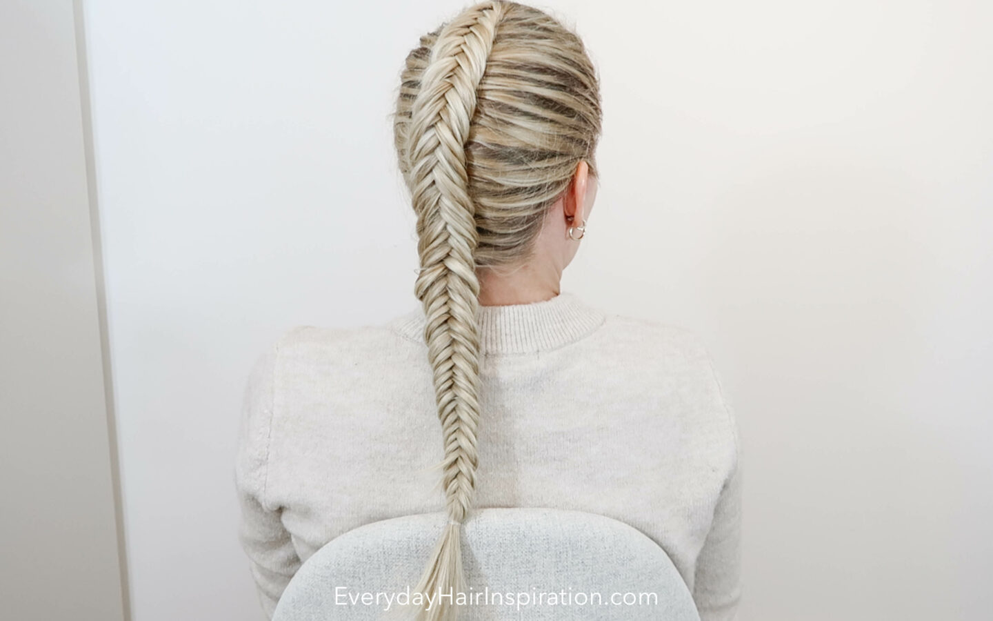 Blonde girl with her back to the camera with a single dutch fishtail braid in her hair, looking to the right.