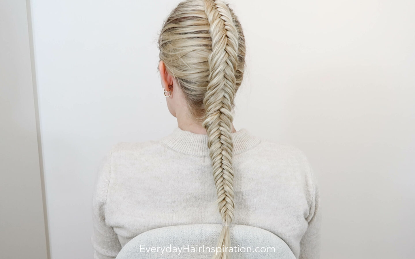 Blonde girl with her back to the camera with a single dutch fishtail braid in her hair, looking to the left.