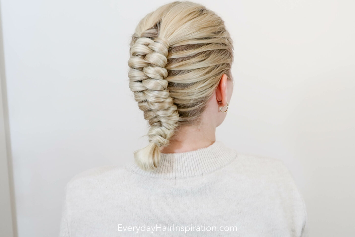 Blonde girl with a dutch infinity braid in her hair, with a small bun at the end.
